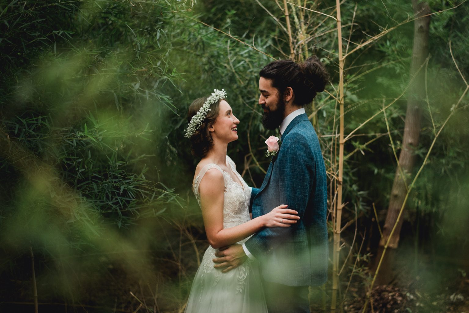 bride with baby's breath crown and groom with long hair cuddle close on their wedding day in austin texas