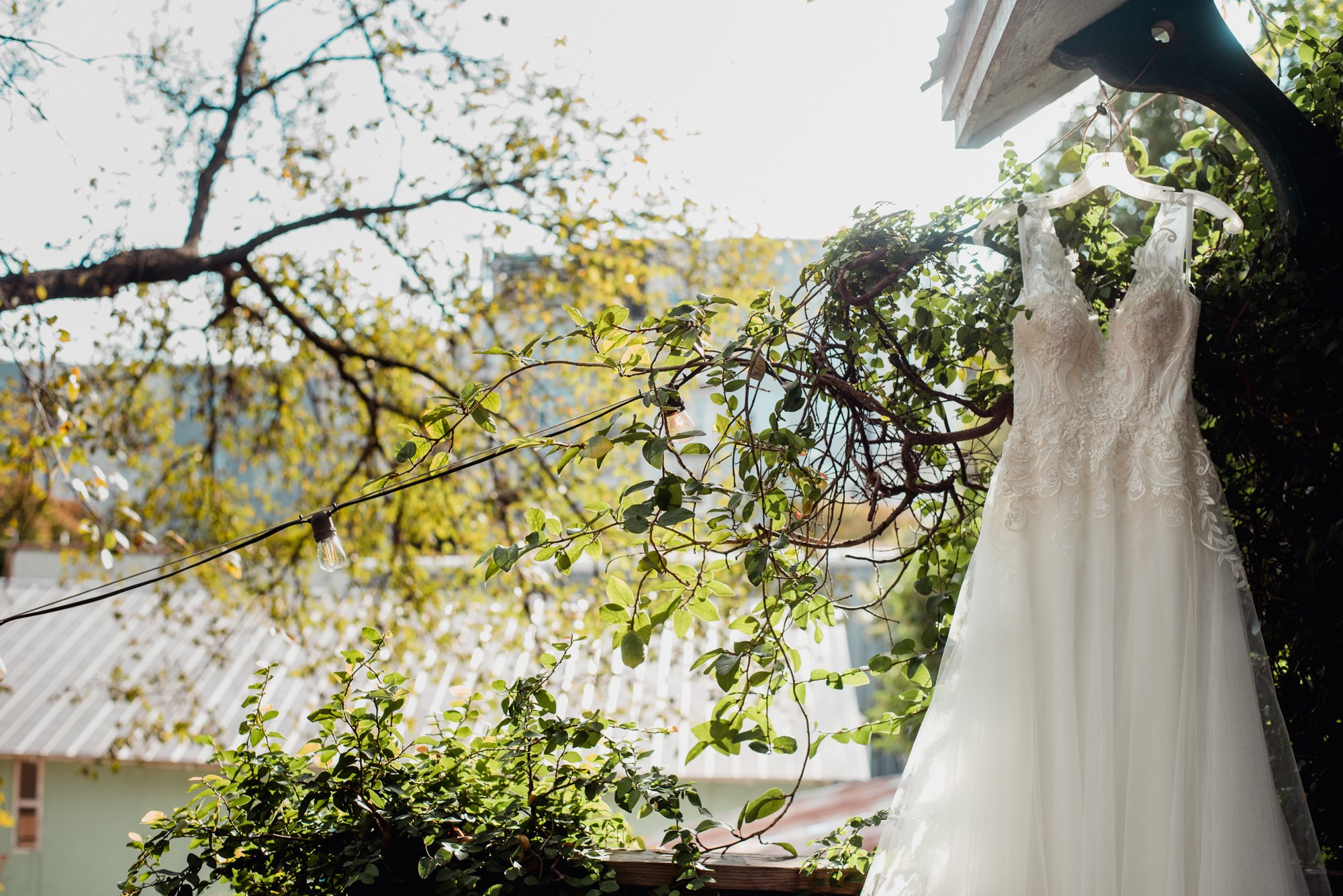 bhldn lace wedding dress hangs outside a house on a wire