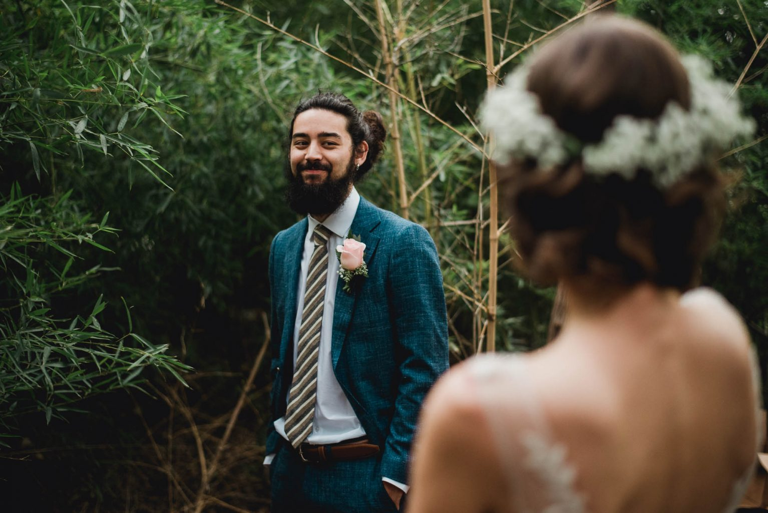 groom takes a glance at his bohemian bride at an Austin wedding
