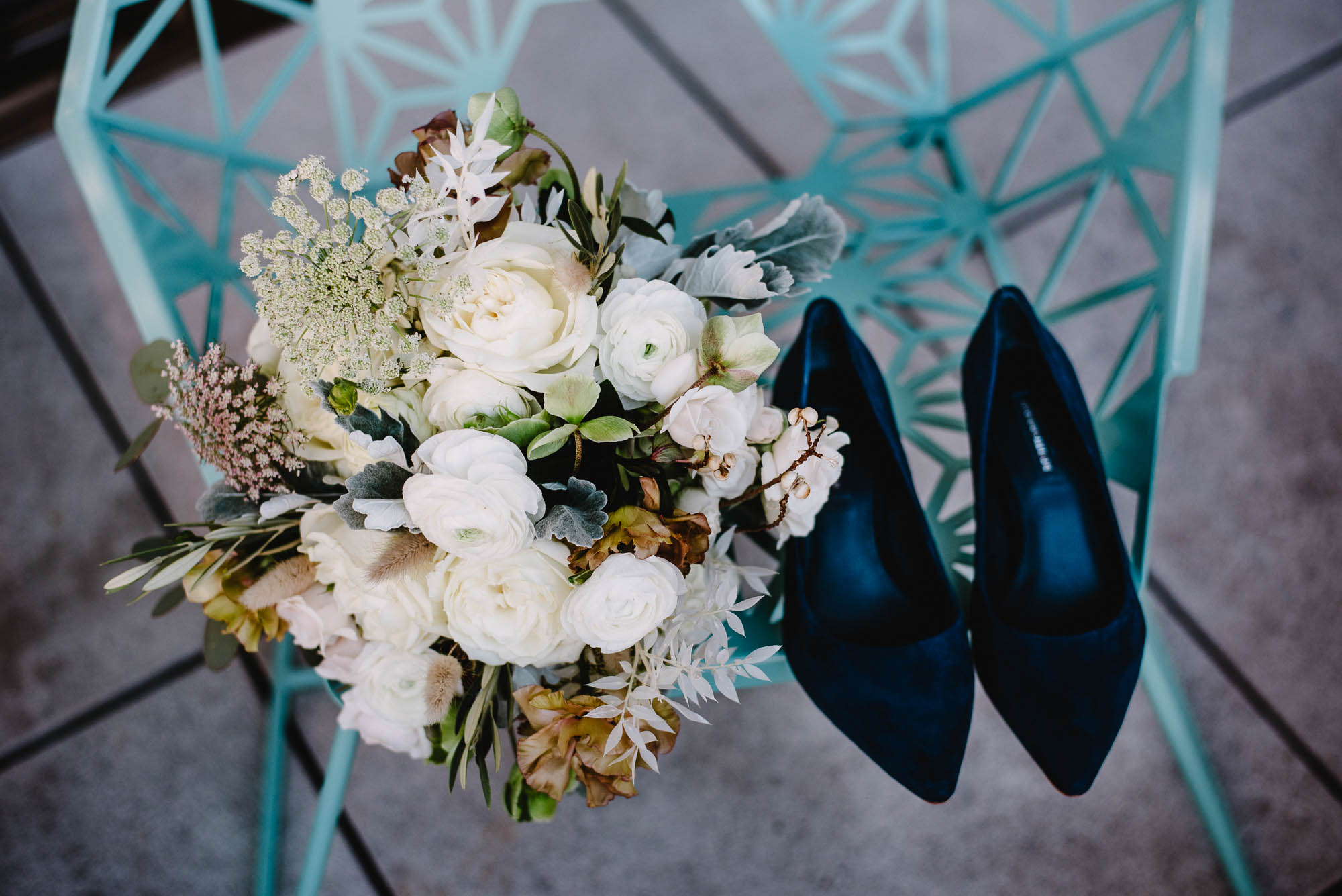 white bouquet with ranunculus and greenery next to a pair of navy blue wedding shoes at the south congress hotel in austin