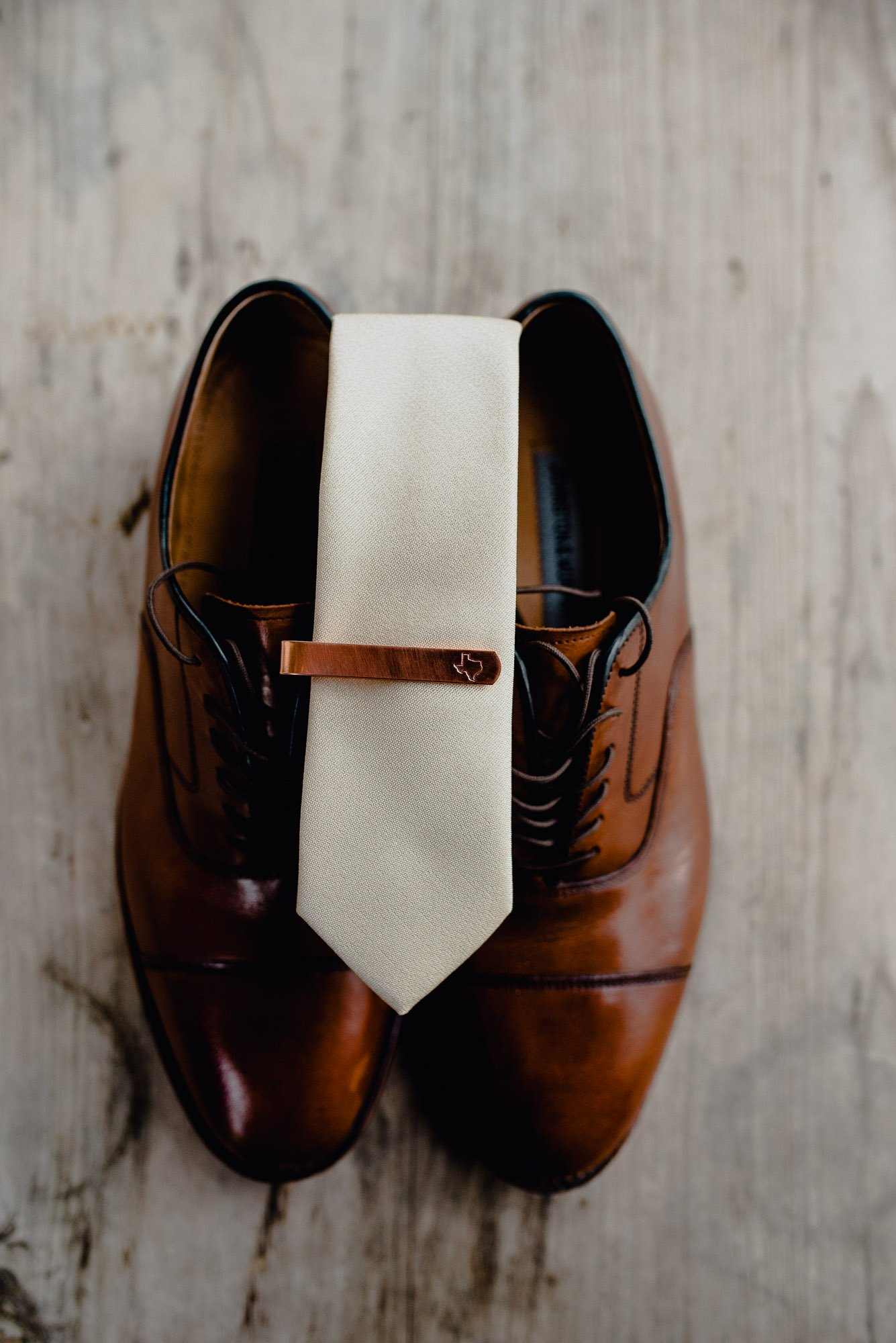 groom's details, tie and texas tie clip on a brown pair of shoes at a texas wedding