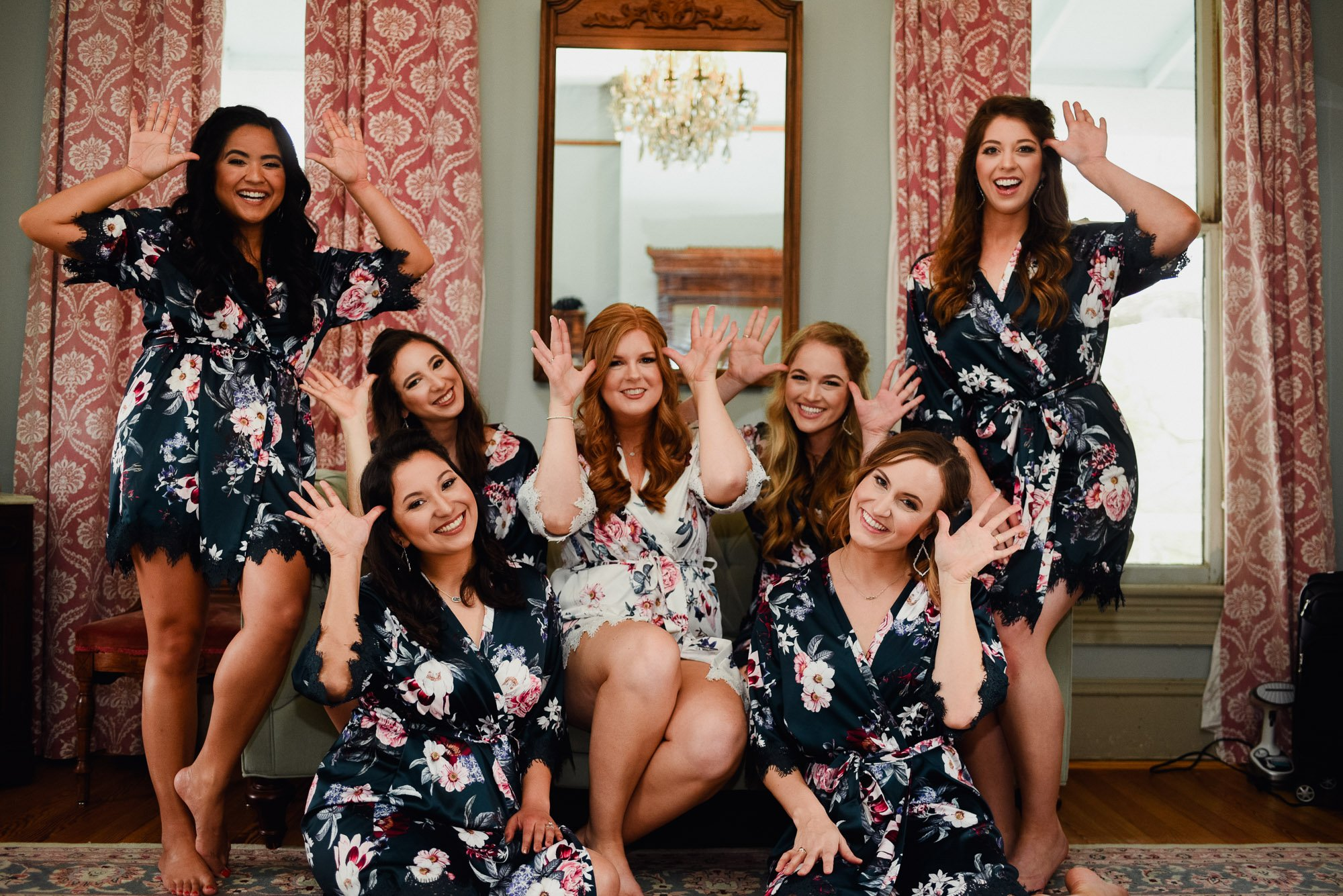bridesmaids being goofy in matching floral robes at a barr mansion wedding