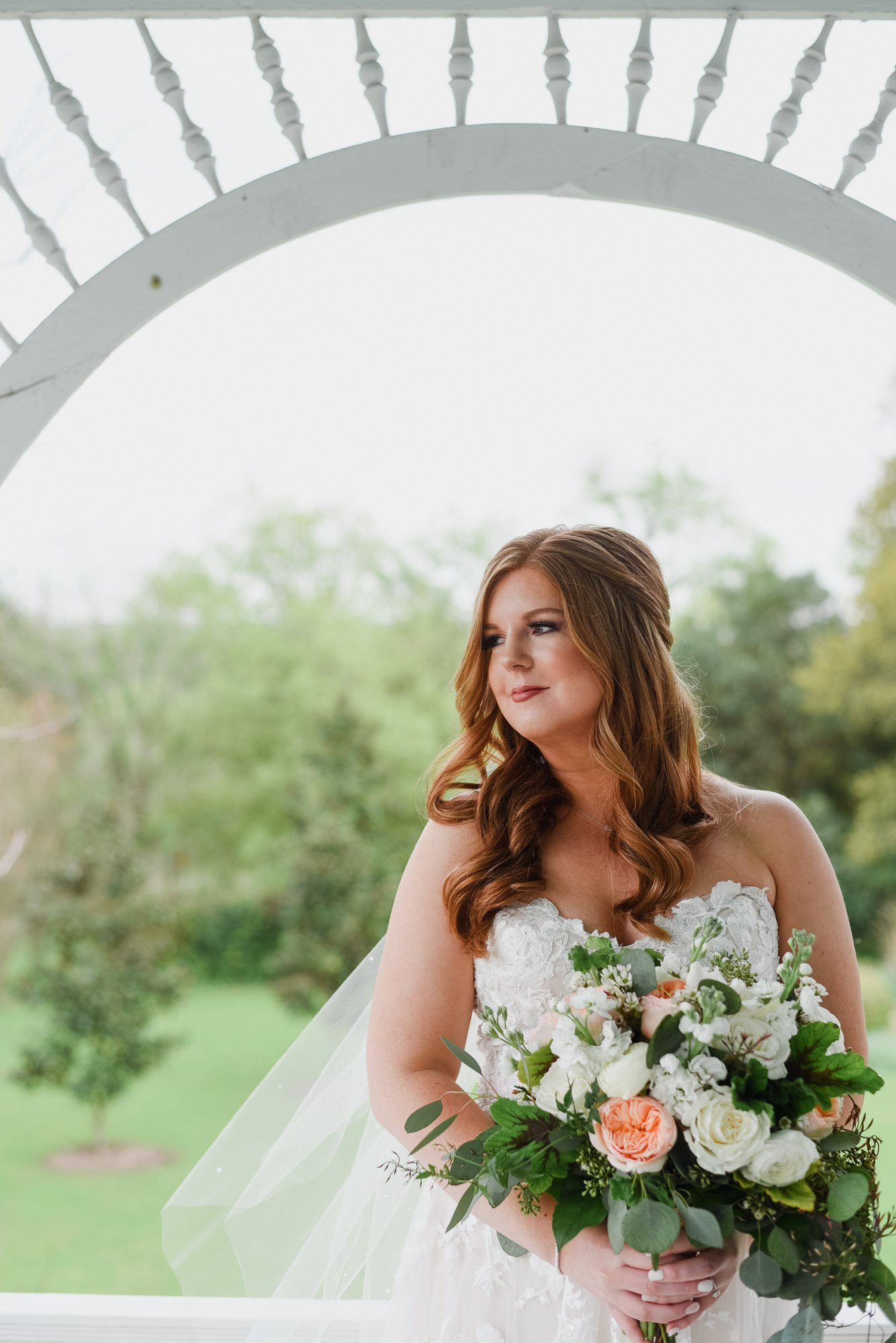 kate looks gorgeous on her wedding day holding a bouquet of peach roses and white flowers with tons of greenery at the barr mansion