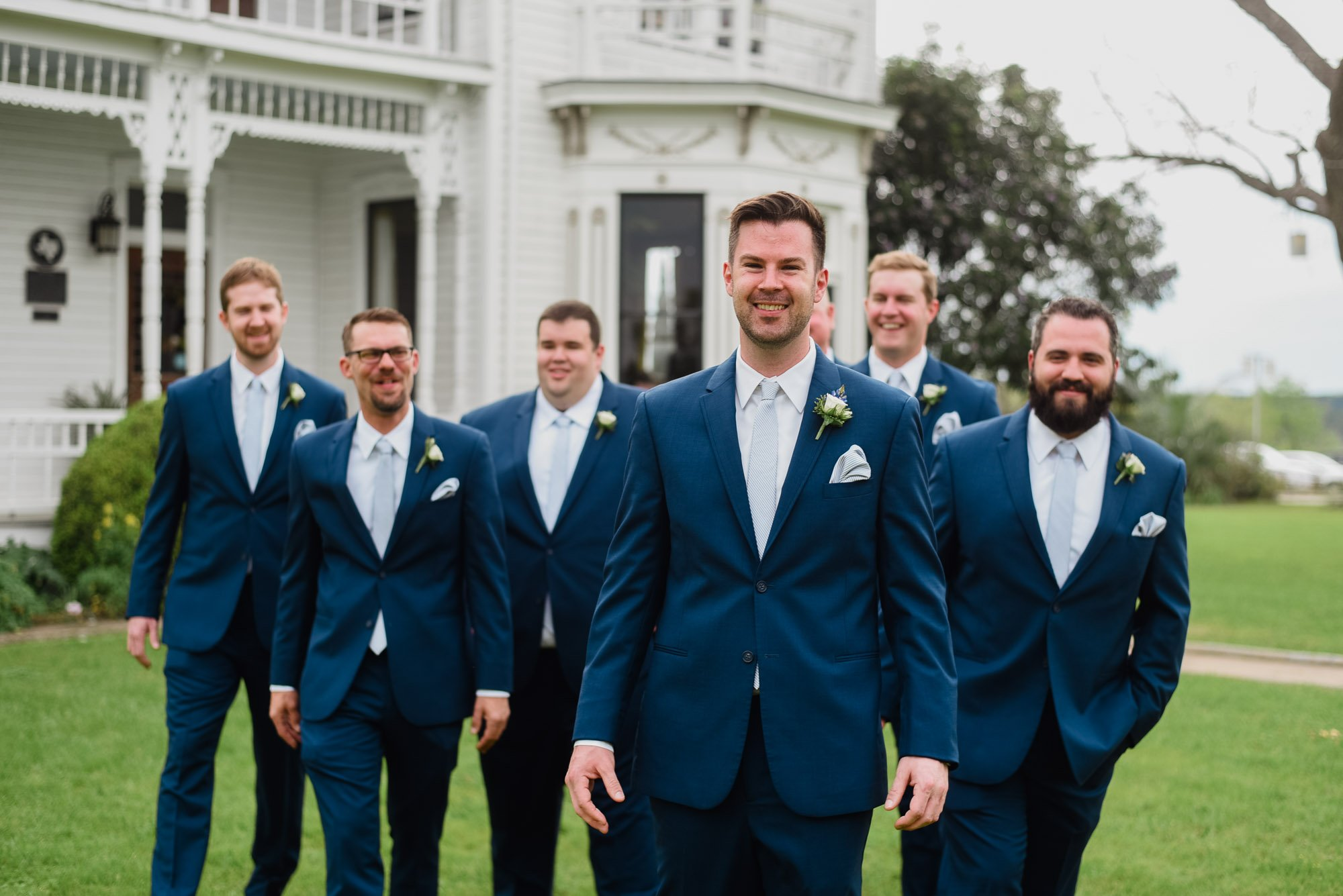 groomsmen and groom in all blue suits outside the barr mansion
