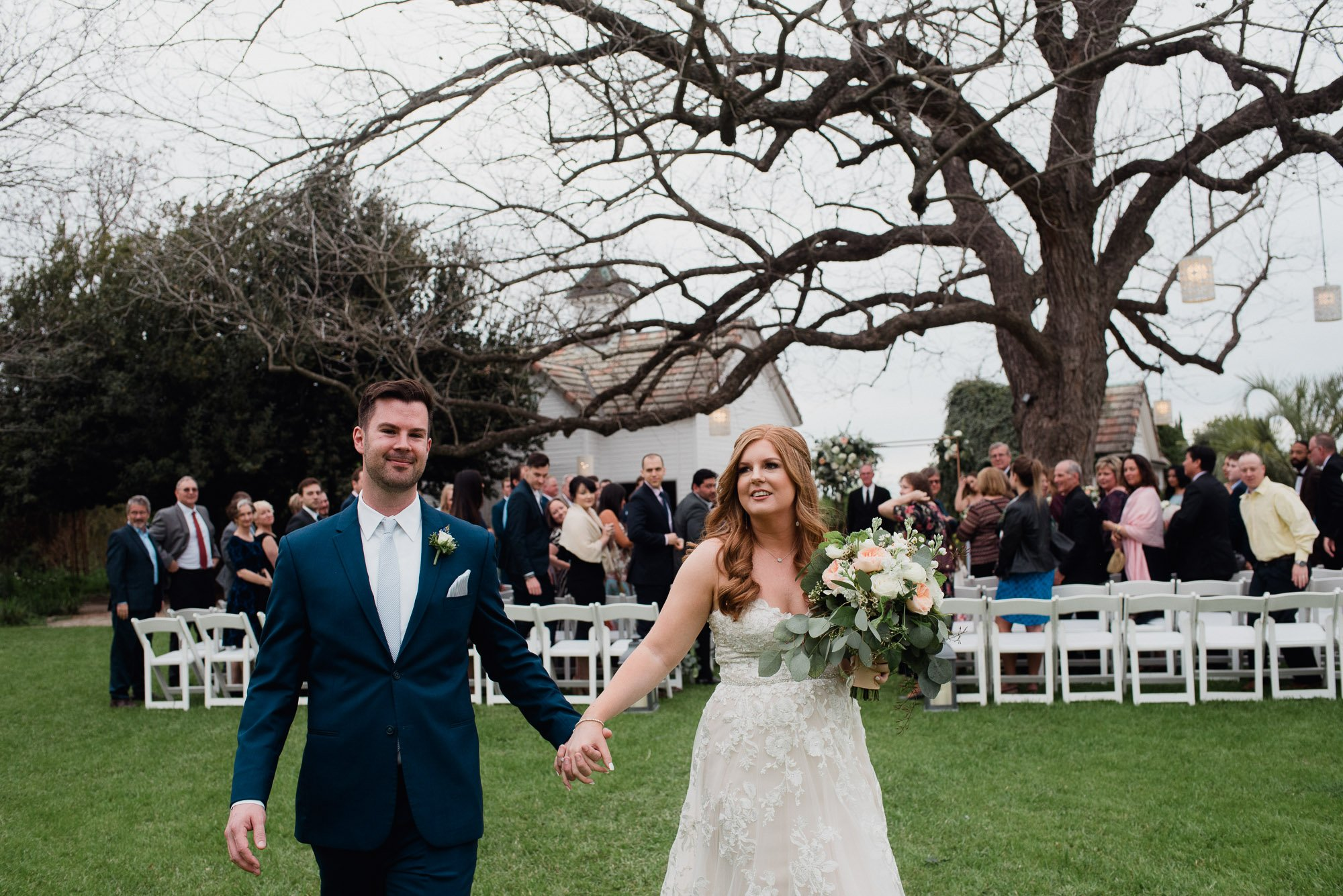 bride and groom leave their wedding ceremony at the barr mansion in austin hand in hand