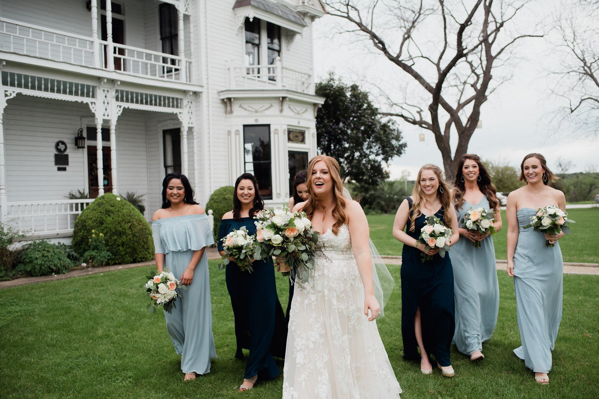 bridesmaids in mismatched blue dresses walk in a group at a spring wedding in austin
