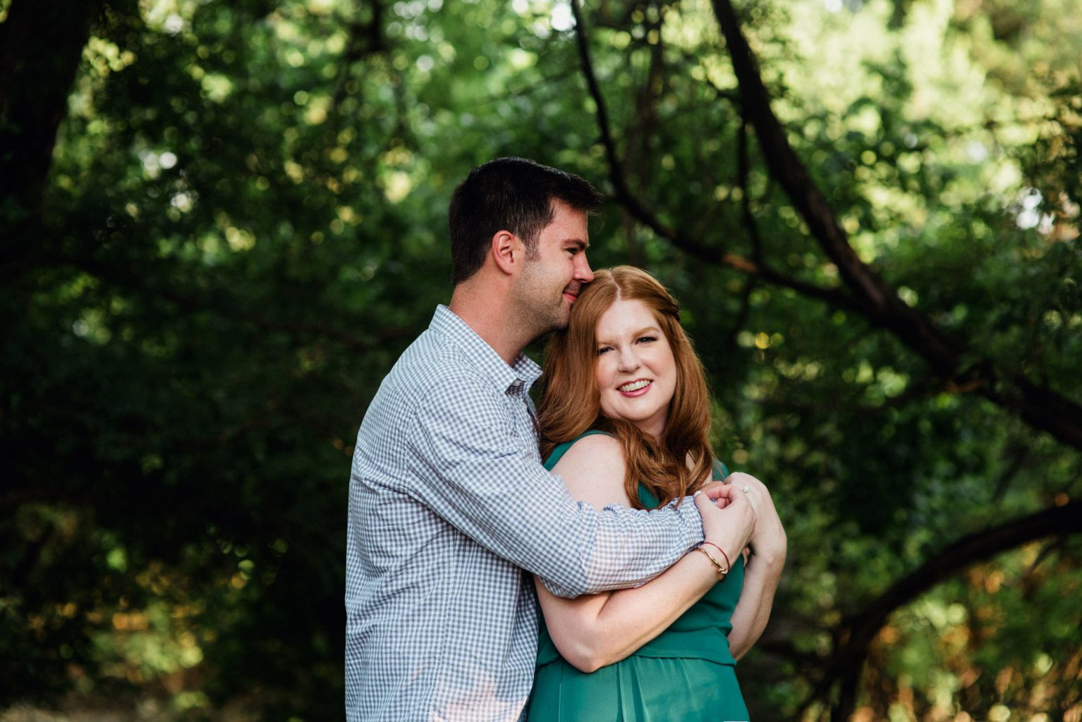 a man and woman in a green dress pose for engagement photos in greenery