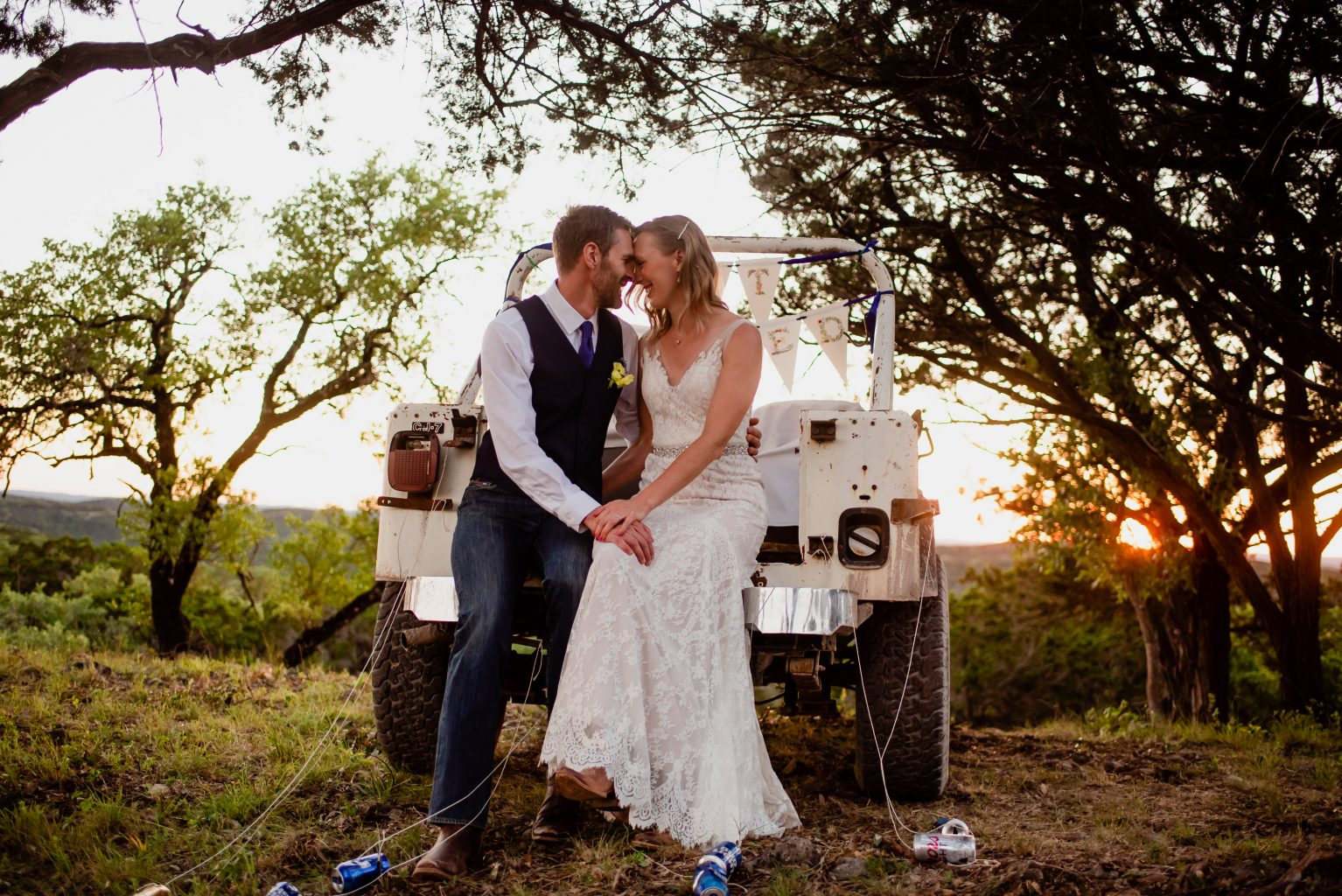 "wedding portraits on the back of a vintage jeep with a ""just married banner"" at an intimate wedding in Boerne, Texas"