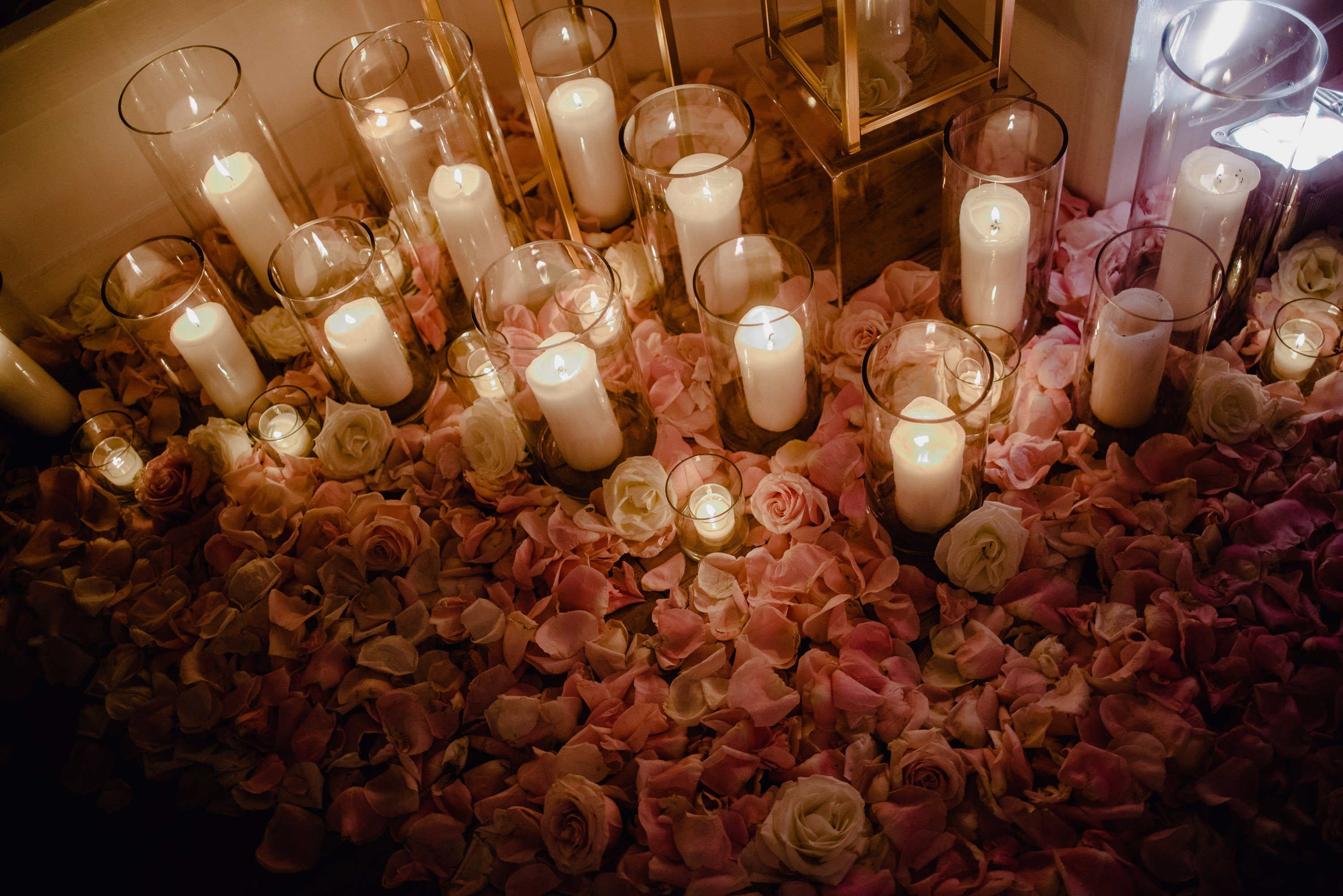 dozens of pink rose petals and white taper candles decorate the floor at the Allan House winter open house