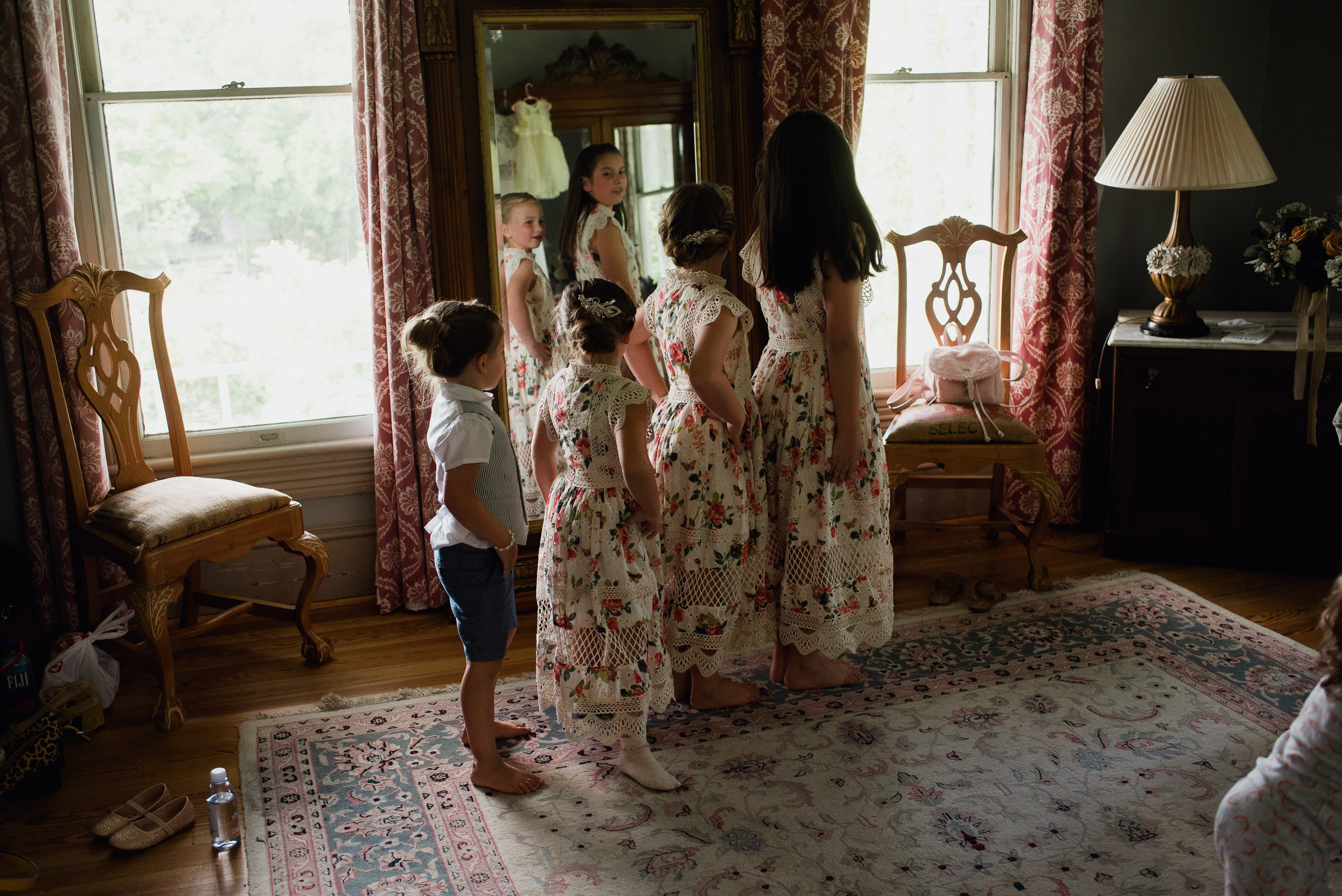 flower girls practice dancing in front of a mirror