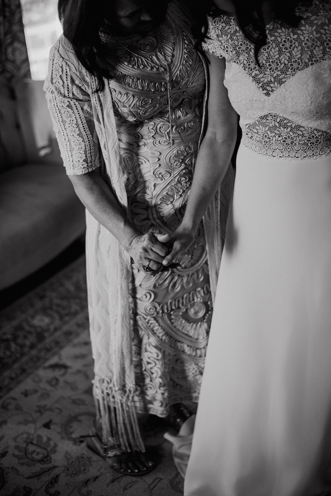black and white detail of mom and daughter hands holding during a wedding getting ready at the barr mansion