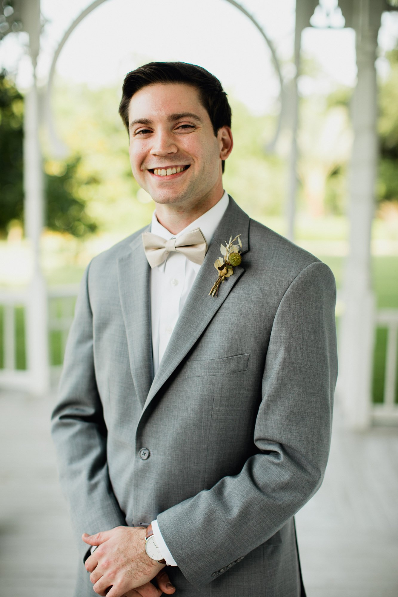 groom in a grey suit and gold bowtie smiles for a portrait before his wedding at the barr mansion in austin texas