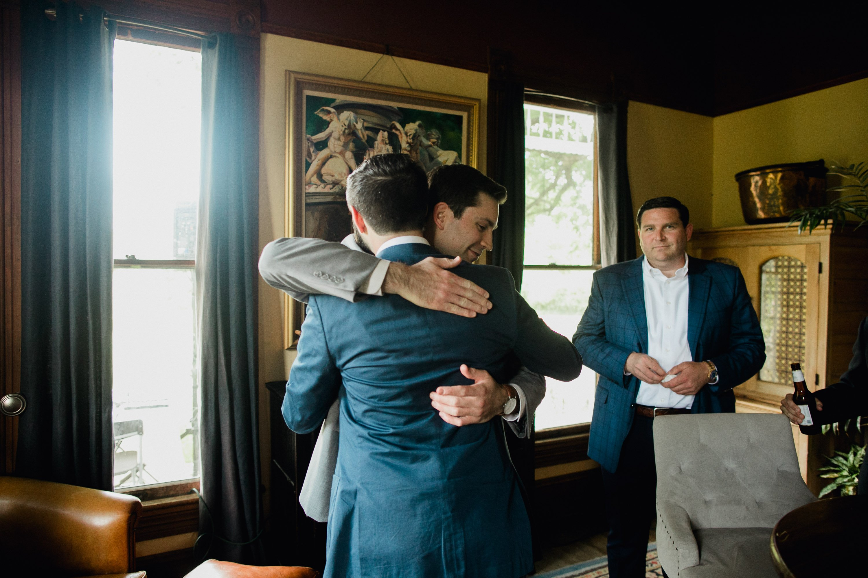 candid photo of a groom greeting friends during the getting ready part of the wedding day at Barr mansion