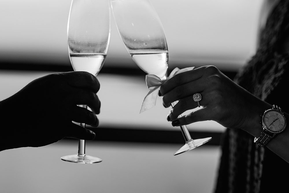 newly engaged couple toasts with champagne in black and white