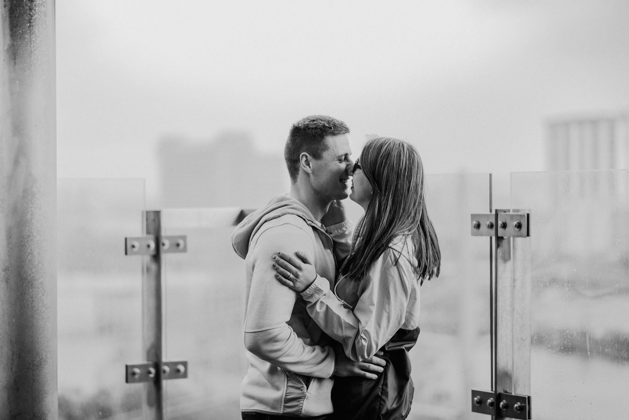 black and white photo of a couple in causual wear about to kiss
