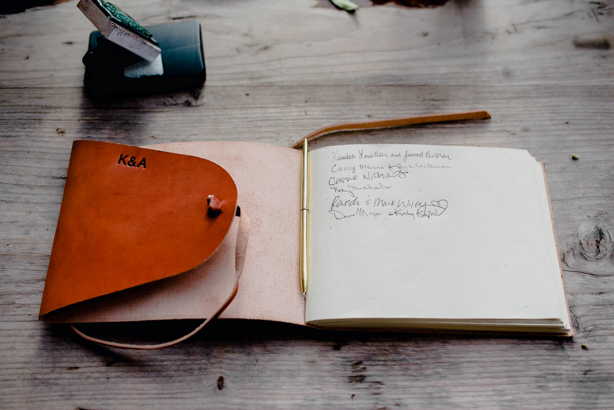 leather journal acts as a sign in book with the couples' initials embossed on cover
