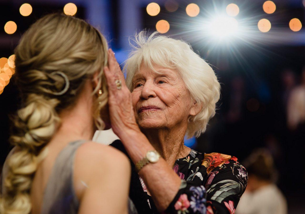 grandma at wedding touching bride's face